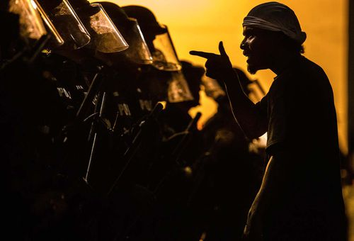 A protester vents at a line of Tucson Police Officers in riot gear at Cushing Street and Church Avenue in Tucson Arizona