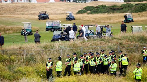 Just metres from where he was playing, Scottish police kept a close eye on protesters. Picture: AAP