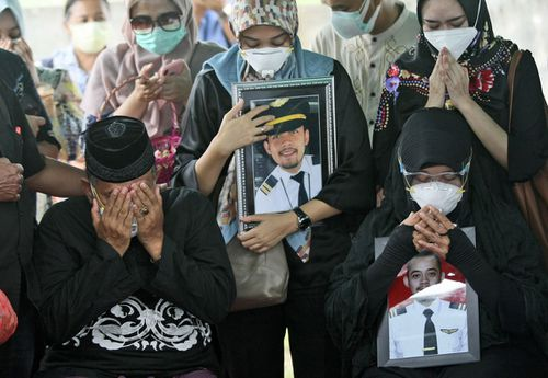 Relatives weep as they pray during the burial of Fadly Satrianto, a victim of the crash of Sriwijaya Air flight SJ-182 in Surabaya, East Java, Indonesia, Friday, Jan. 15, 2021