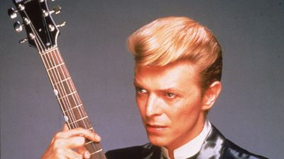 1980s studio portrait of British rock singer David Bowie wearing a black satin suit and holding a red guitar. (Getty)