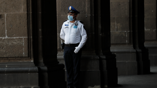 A police officer wearing protective gear against the spread of the new coronavirus, stands guard outside the mayor's office, in the historic center of Mexico City, Wednesday, April 1, 2020.