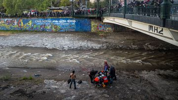Paramedics attend a youth who fell to the Mapocho river from a bridge during a police charge on protesters in Santiago, Chile.