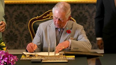Prince Charles signs a visitor's book in Malaysia, 2017