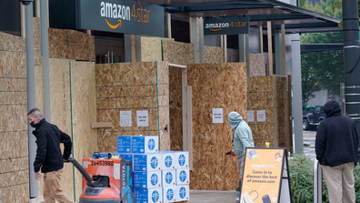 People walk into a business being boarded-up Tuesday, Nov. 3, 2020, in downtown Seattle. (AP Photo/Ted S. Warren)