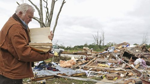 Robert Scott looks through a family Bible that he pulled out of the rubble from his home.