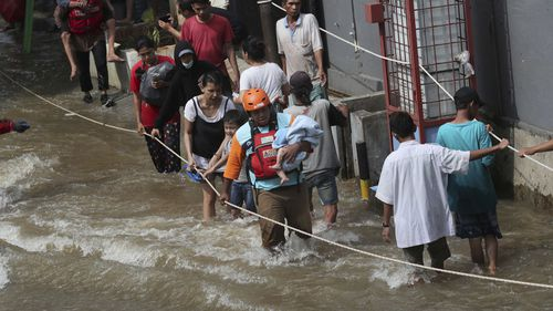 A rescuer, centre, evacuates a baby in flooded neighbourhood in Tanggerang outside Jakarta, Indonesia, Thursday, Jan. 2, 2020.