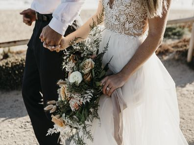 A close-up of bride and groom walking on path at the coast