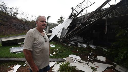 Dave McInerney beside the wreckage of his business at Shute Harbour. (AAP)