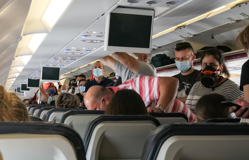 Passengers in face masks board a plane