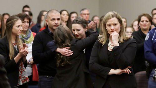 Former gymnast Rachael Denhollander, center, is hugged after giving her victim impact. (AAP)