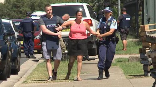 The owner of the sign-making business, Chantelle Tonna, being helped away from the scene by police. (9News)