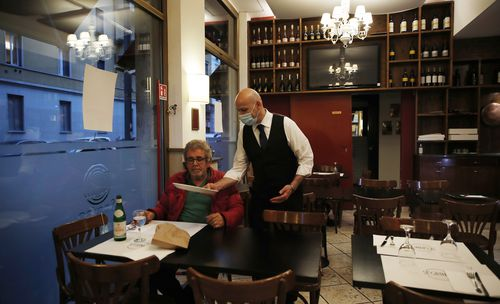 """In this photo taken on Tuesday, May 19, 2020, a waiter tends to a customer at the """"La Rotonda di Segrino"""" restaurant in Milan, Italy."""