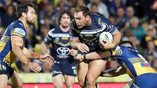 Bolton (centre) breaks a tackle in a game against the Parramatta Eels.