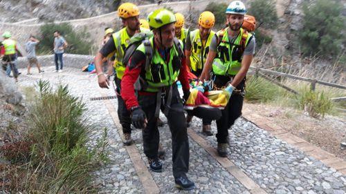 Survivors are brought out the flooded gorge by rescue teams.