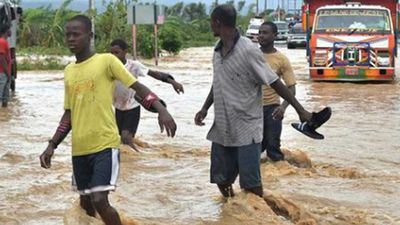 Men wade through the floodwaters after the storm front dumped torrential rain on Haiti. (AP)