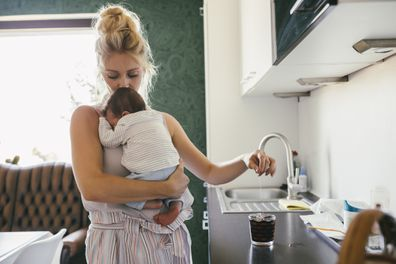 Mother holding newborn baby in kitchen while making tea