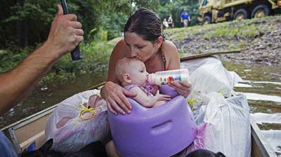 Danielle Blount kisses her 3-month-old baby Ember as she feeds her while they wait to be evacuated by members of the Louisiana Army National Guard near Walker. (AP)