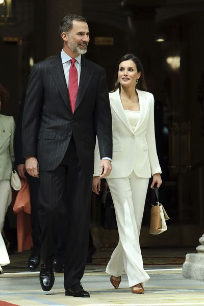 <p>Queen Letizia of Spain in a pant suit by Carolina Herrera with her husband King Felipe VI for an event at the royal palace of El Pardo, May, 2018&nbsp;</p>