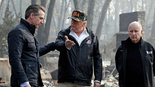 President Donald Trump talks with Governor Gavin Newsom, left, as California Governor Jerry Brown listens during a visit to a neighborhood impacted by the Camp wildfire in Paradise, California.