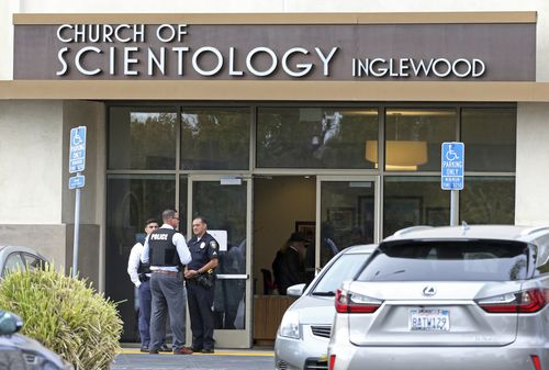 Police stand by outside and investigators work inside the entrance to the Church of Scientology in Inglewood, after a sword wielding man was shot dead by officers. (AP Photo/Reed Saxon)