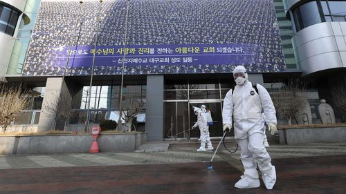 Health workers disinfect the footpath outside the Shincheonji Church of Jesus, a cult in South Korea.