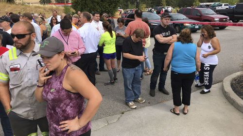 Parents gather in the parking lot behind Freeman High School in Rockford, Wash. to wait for their kids, after a deadly shooting at the high school Wednesday, Sept. 13, 2017. (Dan Pelle/The Spokesman-Review via AP)