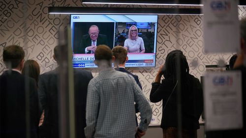 Staff in the green room watch a television screen showing presenters Andrew Neil and Michelle Dewberry broadcast from a studio, during the launch event for new TV channel GB News.