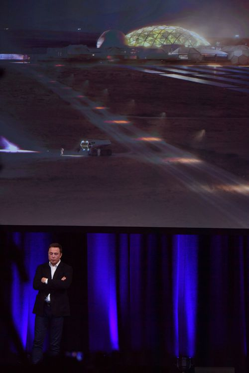 CEO of Tesla and Director of SPACEX, Elon Musk is seen delivering a presentation, with a representation of what he imagines a human colony on mars to look like on the screen behind him