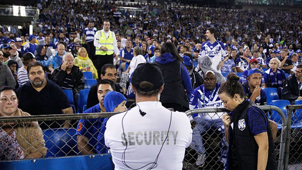 A security guard watches the crowd following the bottle throwing incident at Belmore Oval. (Getty)