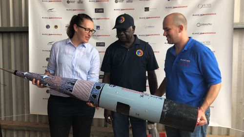 ELA CEO Carley Scott with Djawa Yunupingu (Gumatj Corporation Board member), Blake Nikolic (CEO Black Sky Aerospace). The nosecone design is by Dorothy Yunupingu of Djulpan, despicting the seven sisters.