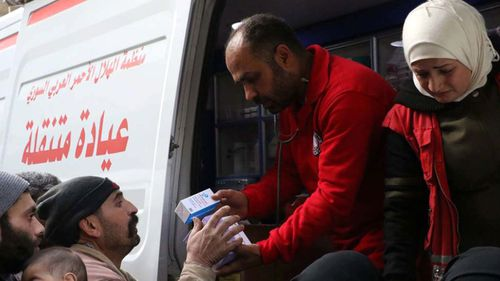 Aid workers hand out supplies to people. (AP).
