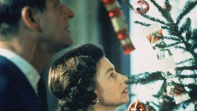 The Queen and Prince Philip looking at Christmas tree.