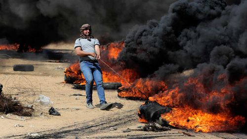Palestinian protesters take part during clashes with Israeli soldiers at the border fence. (AAP)