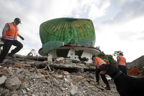 Yesterday, rescuer officers worked to clear the rubble from a local mosque that was pancaked in the earthquake. Picture: AP.
