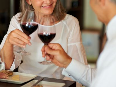 Elderly woman toasting wine with her husband at a smart restaurant