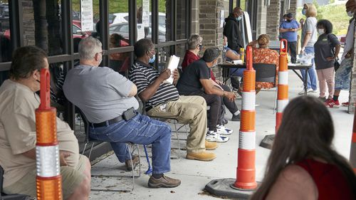US job seekers exercise social distancing as they wait to be called into the Heartland Workforce Solutions office in Omaha, Neb. (July 2020)