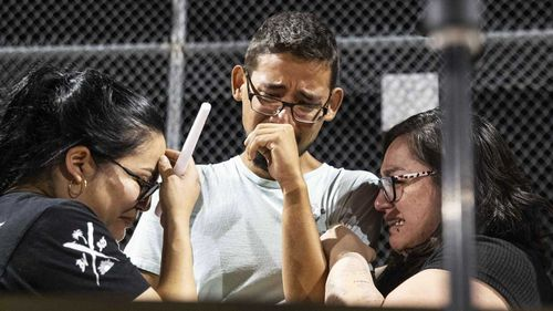El Paso Wal-Mart employees weep at a vigil after the massacre in their store.