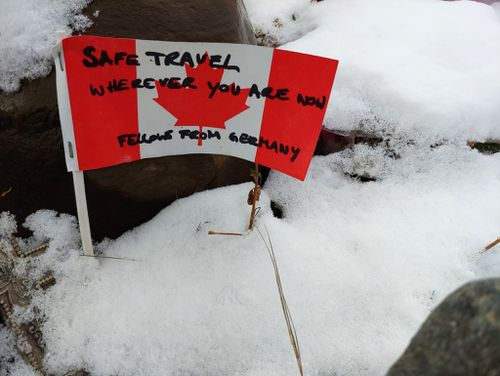A handwritten note from a traveller sits in fresh snow at the memorial on Alaska Highway, in rugged northern British Columbia.