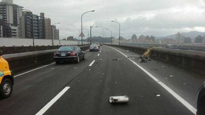 Metal scraps from the plane's wing and the taxi were left scattered across the highway, which crosses New Taipei City's Keelung River. (TVBS News)