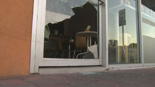 The smashed in door of one of the businesses.