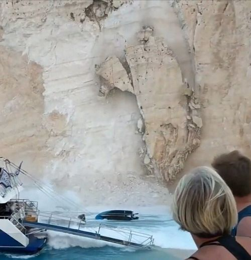 A rock wall has peeled off the cliff face surrounding the popular Greek beach of Navagio injuring tourists.