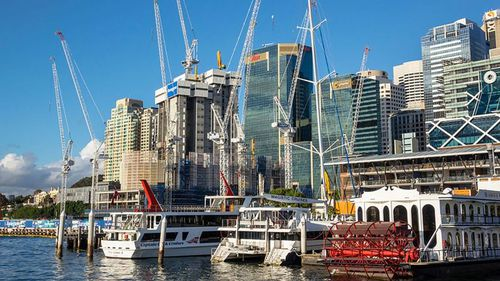 The 24-year-old who illegally climbed to the top of a Darling Harbour crane and jumped off has been charged. (Getty)