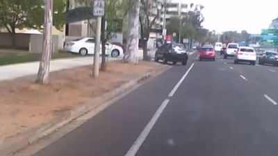 Heart-stopping moment a driver almost clips cyclist on footpath