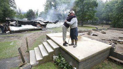 Flood victims embrace in White Sulphur Springs. (AAP)