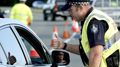 A motorist  is given the thumbs up by a police officer after being stopped at a checkpoint on the Gold Coast Highway at Coolangatta on the Queensland/NSW border,