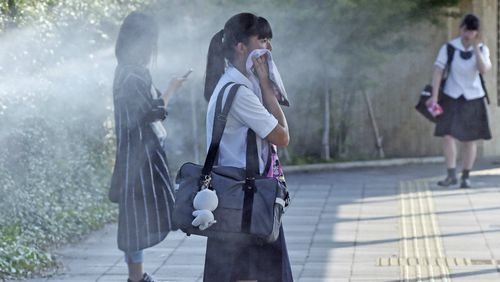 A high school student and other stand at a mist spray point for cooling while the maximum temperature exceeds 40 degrees Celsius in Tajimi City, Gifu Prefecture. Picture: AAP