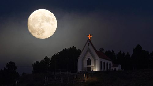 A larger-than-normal moon appears alongside a church in Portugal's north. (AAP)