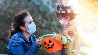 Woman with her son about to trick-or-treat while wearing face masks