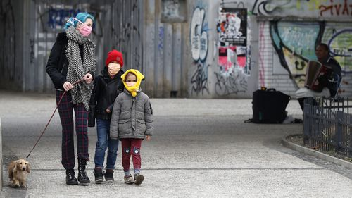 A woman with her children walk their dog in Prague, Czech Republic, amid the coronavirus pandemic.