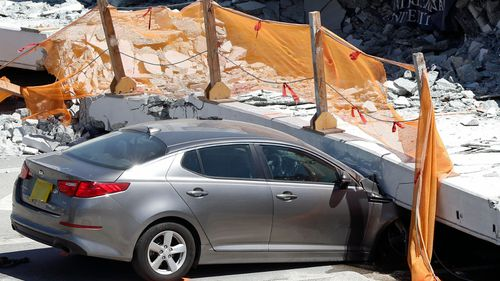 A crushed car beneath a giant slab of concrete and steel. (AP).
